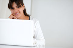 Young woman looking at you in front of her laptop. Portrait of a young woman smiling and looking at you in front of her laptop - copyspace Royalty Free Stock Photos