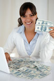 Young woman looking at you holding cash money. Portrait of a young woman looking and smiling at you sitting in front of her laptop with plenty of cash money Stock Photos
