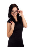 Young woman looking at you over glasses Royalty Free Stock Images