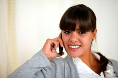 Young woman looking at you speaking on cellphone Stock Images