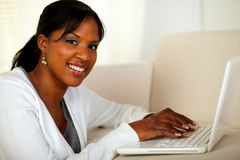 Young woman looking at you while working on laptop Stock Photos