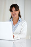Young woman looking at you while working on laptop Royalty Free Stock Photography