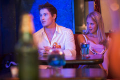 Young woman looking at a young man in a nightclub stock image