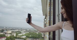 Young woman lookingfrom the window and makes selfie on the smartphone. stock footage
