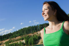 The young woman looks afar. The beautiful smiling young woman in a green vest Stock Images