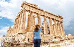 Young woman looks at Ancient Greek Parthenon on the Acropolis of Athens, Greece. This place is a top tourist attraction of Athens. Adult girl traveler visits royalty free stock photo