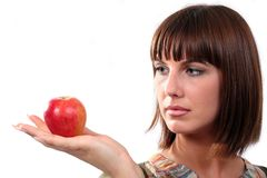 Young woman looks at an apple Royalty Free Stock Photo