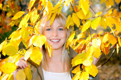 Young woman looks through autumn leaves. Beautiful young blond woman looks through autumn leaves stock photos