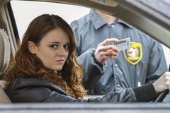 Young woman looks away after being pulled over by police Stock Photography