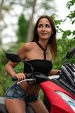 A young woman looks away in surprise, sitting behind the wheel of a motorcycle.  stock image