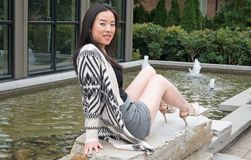 Young gal sits in sunshine by landscape water feature. Young woman looks back at the camera as she stretches her legs and high heeled shoes next to a building royalty free stock photography