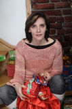 Young woman looks at  Christmas bag with gifts Royalty Free Stock Photo