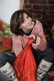 Young woman looks at  Christmas bag with gifts Royalty Free Stock Image