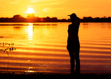 Young woman looks into distance waiting for someone at sunset Royalty Free Stock Photos