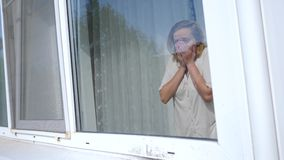 A young woman looks frightened from behind the curtains into the window, she is frightened by the incident that happened