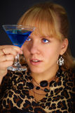 Young woman looks at glass with unusual cocktail Stock Image