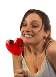 Young woman looks at heart shaped lollipop. Isolated over white Royalty Free Stock Image