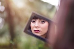 Young woman looks in her mirror. Illuminated by the rays of the sun Stock Image