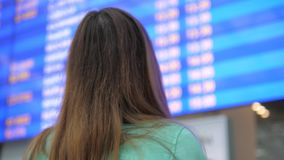 Young Woman Looks At The Information Board Of Departures At The Airport. Close-up of a young brunette woman traveling. Looks at the information board of stock video