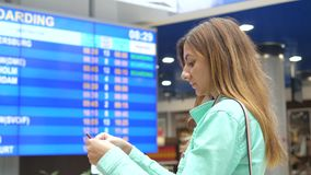 Young Woman Looks At The Information Board Of Departures At The Airport. A sweet traveling young brunette woman. Looks at the information board of departures stock video footage