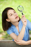 Young woman looks through magnifier Royalty Free Stock Photos