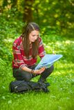 A young woman looks at a map while hiking. A young woman with a backpack looks at a map while hiking in the green forest Stock Photography
