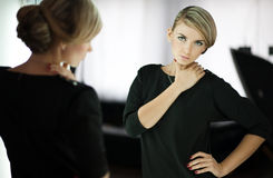 Young woman looks in a mirror Stock Images