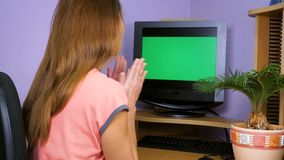 A young woman looks into the monitor, rejoices and claps her hands. A young woman sits at a computer desk, looks at the monitor, rejoices and claps her hands stock footage