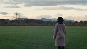 Young woman looks at mountains in autumn stock video footage