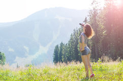 Young woman looks at the mountains through binoculars, outdoor a Royalty Free Stock Photography