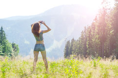 Young woman looks at the mountains through binoculars, outdoor a Royalty Free Stock Photo