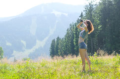 Young woman looks at the mountains through binoculars, outdoor a Royalty Free Stock Photos