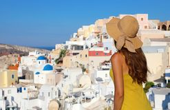 Young woman looks at Oia village in Santorini Island, Greece. The famous resort Greek Island is the main tourist attraction of. Mediterranean. Back view of royalty free stock photography
