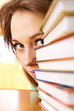 The young woman looks out from for piles of books Stock Images