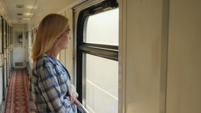 A young woman looks out of the train window. It is in the corridor, the train is moving fast. Dreams and travels stock video footage