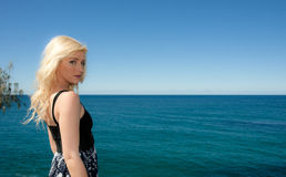 Young woman looks over blue ocean Stock Photography