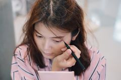Young woman looks into pink pocket mirror and putting eye pencil color on eyes. Makeup beauty care woman stock image