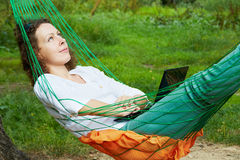 Young woman looks at the sky, lying in hammock. Notebook lies on her stomach stock photography