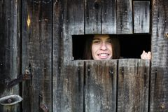 Woman looks and smiles out the little window in the wooden shed stock image