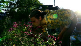 A young woman looks at and sniffs the flowers in the garden of a country house stock footage