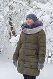 A young woman looks at snow-covered trees,In winter, a woman wears warm knitted hats with a jacket and gloves stock image