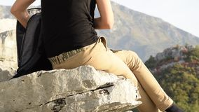 Young woman looks for something in the backpack sitting on the edge of the mountain cliff against the beautiful mountains peaks stock footage