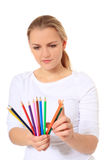 Young woman looks for a special crayon Royalty Free Stock Image