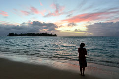 Young woman looks at the sunrise of tropical Island. On Muri lagoon in Rarotonga, Cook Islands Royalty Free Stock Images