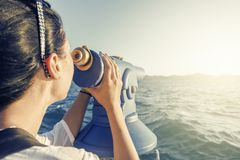 Young woman looks in a telescope or binoculars by the sea. Stock Photography