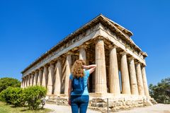 Young woman looks at the Temple of Hephaestus, Athens. Young woman looks at Temple of Hephaestus, Athens, Greece. This ancient Greek structure is one of main Royalty Free Stock Photos