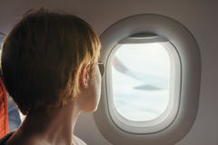 Young woman looks to the illuminator of a airplane during flight. Stock Photos