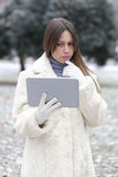 Young woman looks to the tablet in the park Royalty Free Stock Photos