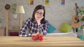 Young woman looks at tomatoes, which cause an allergic reaction.Allergy to tomatoes. Young woman looks at food causing an allergic reaction.Allergy to tomatoes stock footage