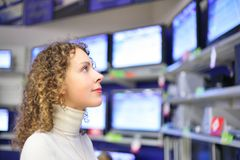Young woman  looks at TVs in shop Royalty Free Stock Photos